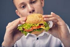 Young man looking at a fresh burger. Beautiful Young man looking at a fresh burger Royalty Free Stock Image