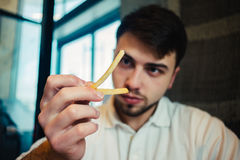 Young man looking at the fries and going to eat. Young man looking at delicious fries and going to eat Royalty Free Stock Photography