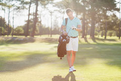 Young man looking at golf club. While standing on field royalty free stock photos
