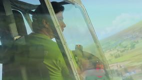 Young man looking at green landscape through flight simulator window, aviation. Stock footage stock video