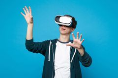 Young man looking on headset touch something like push click on button, pointing at floating virtual screen isolated on. Blue background. People sincere stock photography