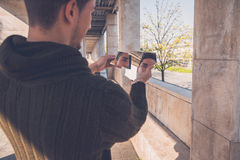 Young  man looking at himself in a broken mirror Royalty Free Stock Photography