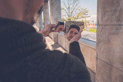 Young  man looking at himself in a broken mirror Royalty Free Stock Photo