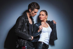 Young man is looking at his girlfriend while takes off her jeather jacket. Punk young men is looking at his girlfriend while takes off her jeather jacket in royalty free stock photography