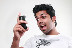 A young man looking his mobile with expression of exitement Stock Images