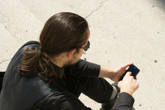 Young man looking at his phone Stock Photography