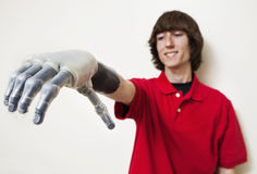 Young man looking at his prosthetic hand over gray background Royalty Free Stock Photography