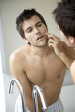 Young man looking at his reflection in a mirror Royalty Free Stock Photo