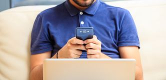 Man looking at his smart phone, sitting comfortably on a sofa Stock Photos