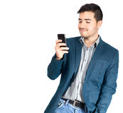 Young man looking at his smart phone. Young hispanic man looking at his smart phone on white background royalty free stock images