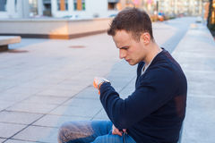 Young man is looking at his watch checking the time. Stock Photo