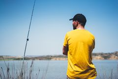 Young man looking on horizont seascape and holds a fishing rod and catches fish in the nature background, hipster fisherman spends royalty free stock photos