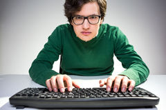 Young man looking intently. Attractive young man looking at the camera intently and using keyboard on white desktop Royalty Free Stock Photography