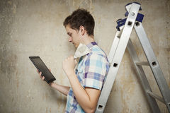 Young man looking on the Internet information about room repairs Stock Photos