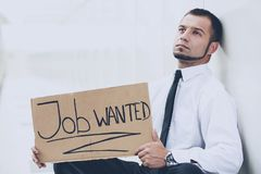 A young man is looking for a job. The guy looks at the job ads. Job wanted. Royalty Free Stock Photo