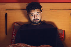 Young man looking at laptop and getting amazed in dark Stock Image