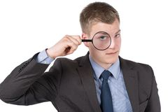Young man is looking through magnifier Stock Image