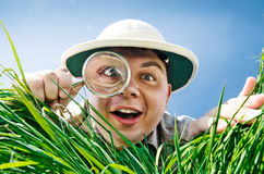 Young Man Looking through a Magnifying Glass. Young Man is Surprised at What He Finds in Grass when Looks through a Magnifying Glass Stock Photography