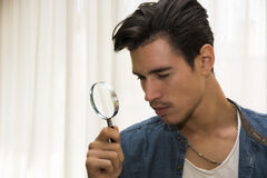 Young man looking through a magnifying glass Stock Images