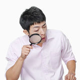 Young man looking through magnifying glass, studio shot Royalty Free Stock Images
