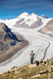 Young man looking at majestic view to Aletsch glacier, the large Royalty Free Stock Images