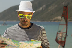 Young man looking at the map on the beach. Royalty Free Stock Photo