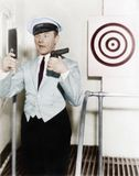 Young man looking at a mirror and aiming at a dartboard with a handgun Stock Photo