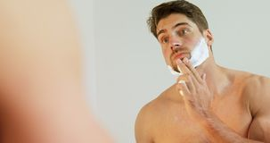 Young man looking into mirror applying shaving foam on his face 4K 4k