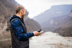 Young man looking at a navigator gps on the bank of a mountain river laying a route while traveling royalty free stock photos