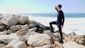 Young man looking at the ocean with hands to head and pointing the finger to the horizon while standing on the rocks. Water splash. Ing agaings the cliffs. Slow stock video