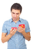 Young man looking into a open small gift Stock Photography