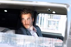 Young man looking out of limousine window stock photos