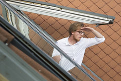 Young man looking out of a rooftop window Royalty Free Stock Photo
