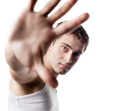 Young man looking out from under raised hand Royalty Free Stock Image