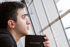 Man Holding Bible Looking Out Window. Young man looking outside with Bible in hand royalty free stock image