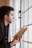 Man Holding Bible Looking Out Window Stock Images