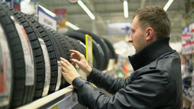 Young man looking over automobile tyres in the automotive department of the hypermarket and trying to choose.  stock video