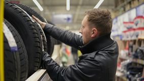 Young man looking over automobile tyres in the automotive department of the hypermarket and trying to choose while. Pressing on them stock video footage