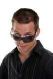 Young man looking over his sun glasses stock photography