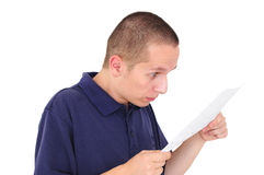 Young man looking at paper with disbelief Royalty Free Stock Images