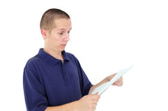 Young man looking at paper with disbelief Royalty Free Stock Photos