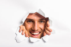 Young man looking through paper rip Stock Photo