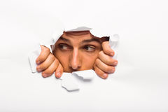 Young man looking through paper rip Royalty Free Stock Images