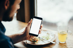 Young man looking at phone, sitting at the restaurant. Back view. Close-up. Vertical image Royalty Free Stock Photos