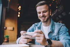 Young man looking at phone, sitting at the restaurant Royalty Free Stock Photo