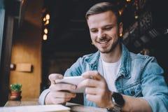 Young man looking at phone, sitting at the restaurant. Young handsome smiling man looking at phone sitting at the restaurant near the window. Attractive guy Royalty Free Stock Photo