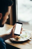 Young man looking at phone, sitting at the restaurant. And having his meal. Back view. Close-up. Horizontal image Stock Images