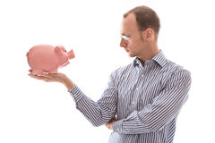 Young man looking at pink piggy bank isolated on white backgroun Stock Photos