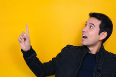 Young man looking and pointing at empty space with surprised face Royalty Free Stock Photo