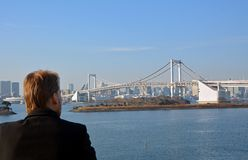 Young man looking at the Rainbow Bridge in Tokyo City.Japan. Royalty Free Stock Images
